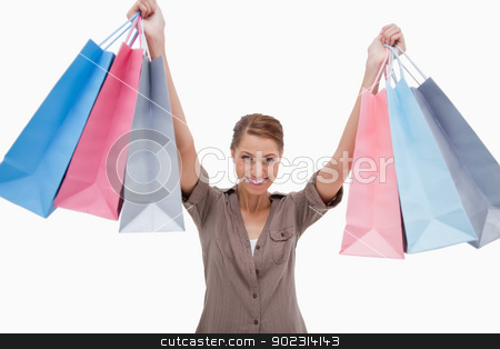 Smiling woman raising her shopping bags stock photo, Smiling woman raising her shopping bags against a white background by Wavebreak Media