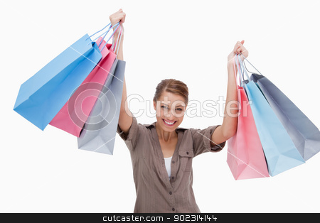 Happy woman raising her shopping bags stock photo, Happy woman raising her shopping bags against a white background by Wavebreak Media