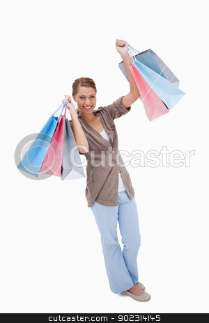 Happy woman with her shopping bags stock photo, Happy woman with her shopping bags against a white background by Wavebreak Media