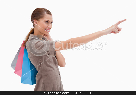 Side view of pointing woman with shopping bags stock photo, Side view of pointing woman with shopping bags against a white background by Wavebreak Media