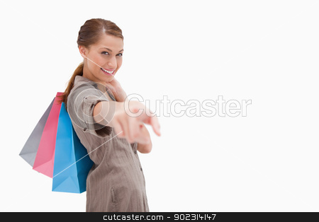 Side view of smiling woman pointing with shopping bags stock photo, Side view of smiling woman pointing with shopping bags against a white background by Wavebreak Media