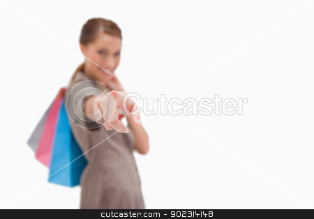 Hand of woman with shopping bags pointing stock photo, Hand of woman with shopping bags pointing against a white background by Wavebreak Media