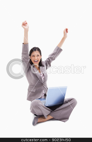Cheering woman sitting with laptop stock photo, Cheering woman sitting with laptop against a white background by Wavebreak Media