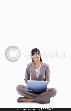 Sitting woman working with laptop stock photo, Sitting woman working with laptop against a white background by Wavebreak Media