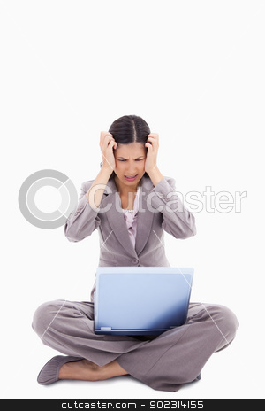 Sitting woman having trouble with notebook stock photo, Sitting woman having trouble with notebook against a white background by Wavebreak Media