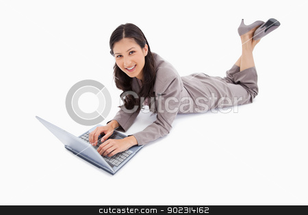 Lying woman with her laptop stock photo, Lying woman with her laptop against a white background by Wavebreak Media