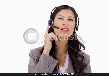 Businesswoman listening to caller with headset stock photo, Businesswoman listening to caller with headset against a white background by Wavebreak Media