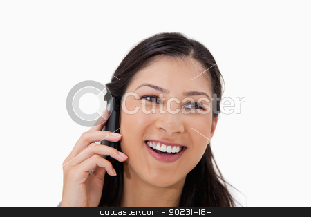 Laughing woman on the cellphone stock photo, Laughing woman on the cellphone against a white background by Wavebreak Media