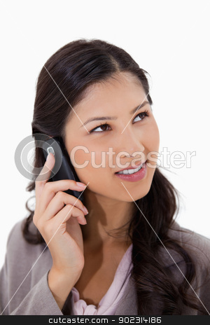 Woman listening to caller on the phone stock photo, Woman listening to caller on the phone against a white background by Wavebreak Media