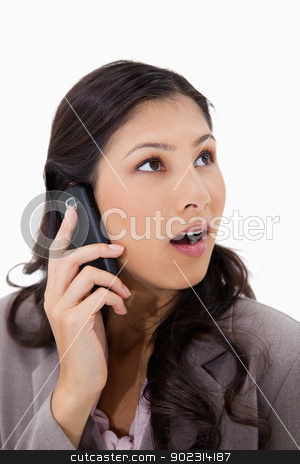 Surprised woman on the phone stock photo, Surprised woman on the phone against a white background by Wavebreak Media