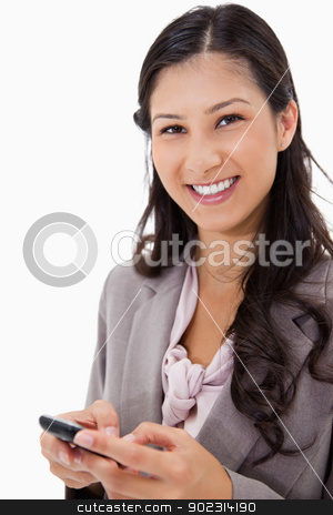 Smiling woman holding cellphone stock photo, Smiling woman holding cellphone against a white background by Wavebreak Media