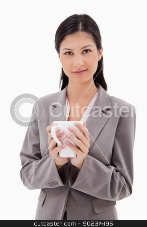 Businesswoman holding cup stock photo, Businesswoman holding cup against a white background by Wavebreak Media