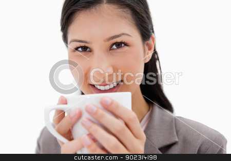Smiling businesswoman holding cup close stock photo, Smiling businesswoman holding cup close against a white background by Wavebreak Media