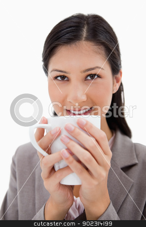 Businesswoman holding cup with both hands stock photo, Businesswoman holding cup with both hands against a white background by Wavebreak Media