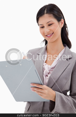 Smiling businesswoman with clipboard stock photo, Smiling businesswoman with clipboard against a white background by Wavebreak Media