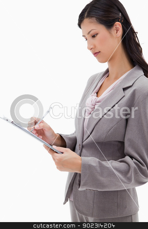 Side view of businesswoman with clipboard stock photo, Side view of businesswoman with clipboard against a white background by Wavebreak Media