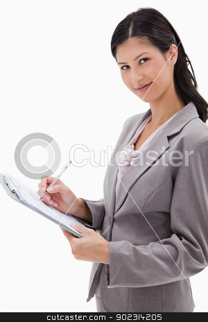 Side view of businesswoman taking notes stock photo, Side view of businesswoman taking notes against a white background by Wavebreak Media