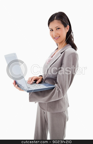 Side view of smiling businesswoman standing with laptop stock photo, Side view of smiling businesswoman standing with laptop against a white background by Wavebreak Media