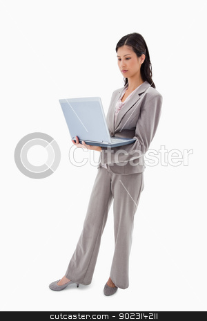 Side view of businesswoman standing with notebook stock photo, Side view of businesswoman standing with notebook against a white background by Wavebreak Media