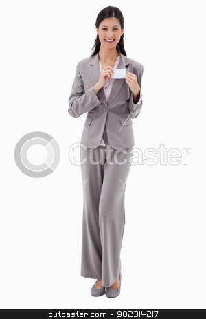 Businesswoman putting on name badge stock photo, Businesswoman putting on name badge against a white background by Wavebreak Media