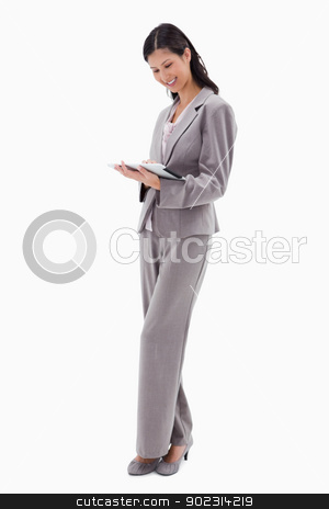 Smiling businesswoman working on tablet stock photo, Smiling businesswoman working on tablet against a white background by Wavebreak Media