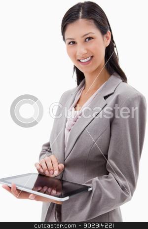 Smiling businesswoman using tablet stock photo, Smiling businesswoman using tablet against a white background by Wavebreak Media