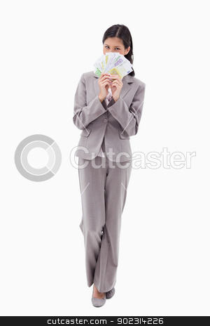 Businesswoman hiding face behind bank notes stock photo, Businesswoman hiding face behind bank notes against a white background by Wavebreak Media