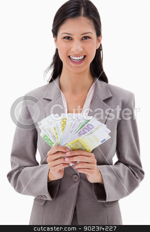 Smiling businesswoman with bank notes in her hands stock photo, Smiling businesswoman with bank notes in her hands against a white background by Wavebreak Media