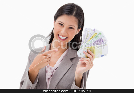 Smiling businesswoman pointing at her money stock photo, Smiling businesswoman pointing at her money against a white background by Wavebreak Media