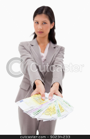 Money being offered by businesswoman stock photo, Money being offered by businesswoman against a white background by Wavebreak Media