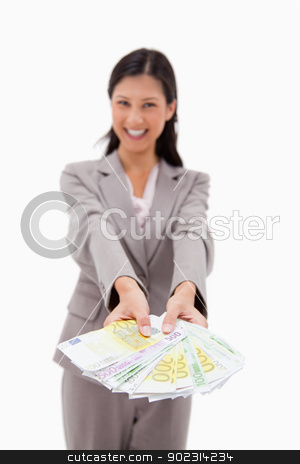 Money being offered by smiling businesswoman stock photo, Money being offered by smiling businesswoman against a white background by Wavebreak Media