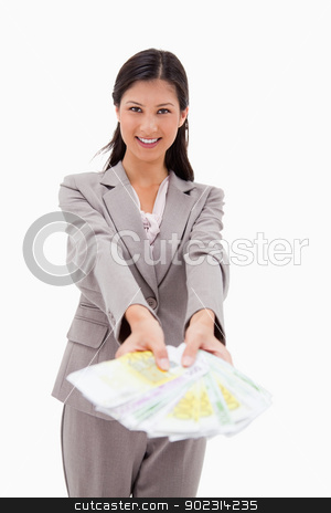 Smiling businesswoman offering money stock photo, Smiling businesswoman offering money against a white background by Wavebreak Media