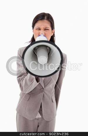 Angry businesswoman yelling through megaphone stock photo, Angry businesswoman yelling through megaphone against a white background by Wavebreak Media