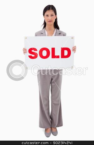 Real estate agent holding sold sign stock photo, Real estate agent holding sold sign against a white background by Wavebreak Media