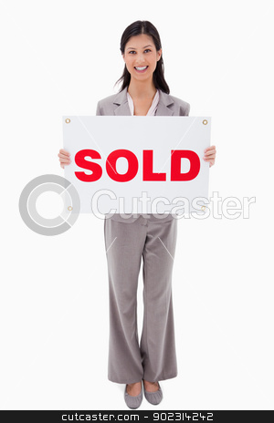 Smiling real estate agent with sold sign stock photo, Smiling real estate agent with sold sign against a white background by Wavebreak Media