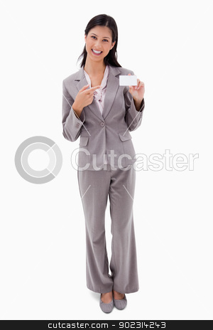 Smiling businesswoman pointing at blank name bagde stock photo, Smiling businesswoman pointing at blank name badge against a white background by Wavebreak Media