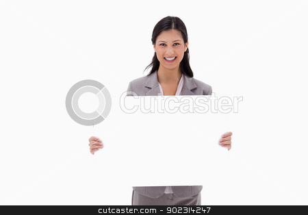 Smiling businesswoman with blank sign board stock photo, Smiling businesswoman with blank sign board against a white background by Wavebreak Media