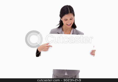 Businesswoman looking and pointing at blank sign board stock photo, Businesswoman looking and pointing at blank sign board against a white background by Wavebreak Media