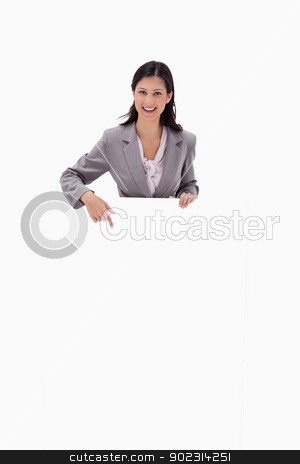 Smiling businesswoman pointing at blank sign stock photo, Smiling businesswoman pointing at blank sign against a white background by Wavebreak Media