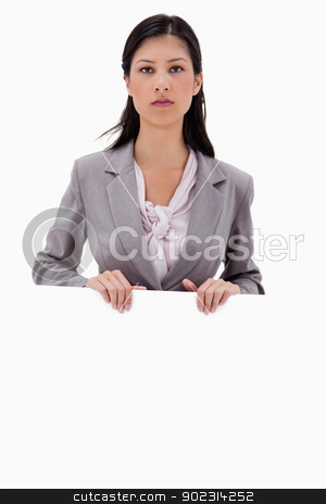 Serious looking businesswoman with blank sign board stock photo, Serious looking businesswoman with blank sign board against a white background by Wavebreak Media