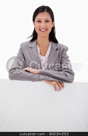 Smiling businesswoman leaning on blank wall stock photo, Smiling businesswoman leaning on blank wall against a white background by Wavebreak Media
