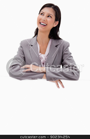 Smiling businesswoman leaning on a blank wall stock photo, Smiling businesswoman leaning on a blank wall against a white background by Wavebreak Media