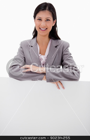 Smiling young businesswoman leaning on blank wall stock photo, Smiling young businesswoman leaning on blank wall against a white background by Wavebreak Media