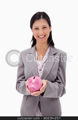Smiling businesswoman with piggy bank stock photo, Smiling businesswoman with piggy bank against a white background by Wavebreak Media