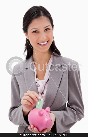 Smiling businesswoman putting money into piggy bank stock photo, Smiling businesswoman putting money into piggy bank against a white background by Wavebreak Media