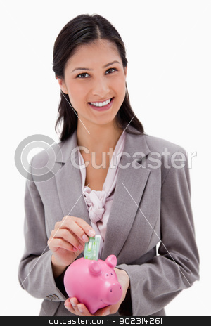 Businesswoman with money and piggy bank stock photo, Businesswoman with money and piggy bank against a white background by Wavebreak Media