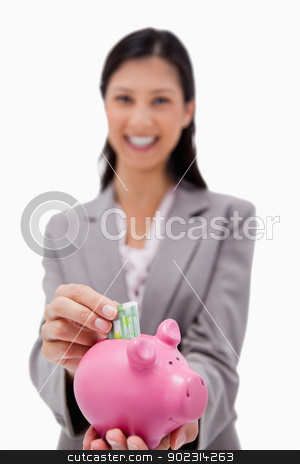 Money being put into piggy bank by smiling businesswoman stock photo, Money being put into piggy bank by smiling businesswoman against a white background by Wavebreak Media