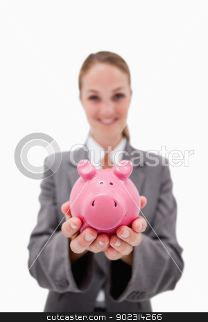 Piggy bank being offered by smiling bank employee stock photo, Piggy bank being offered by smiling bank employee against a white background by Wavebreak Media