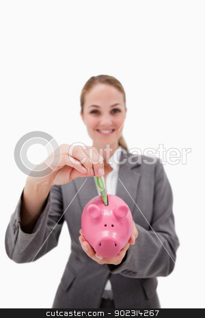 Money being put into piggy bank by smiling bank employee stock photo, Money being put into piggy bank by smiling bank employee against a white background by Wavebreak Media
