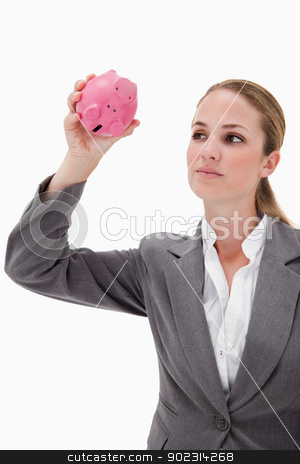 Bank employee taking close look at piggy bank stock photo, Bank employee taking close look at piggy bank against a white background by Wavebreak Media